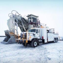 ORO 20M8 mechanic service truck body in white, with Versalift manlift and Stellar 12630 telescopic mechanic crane on Kenworth C500 next to a Bucyrus RH400 excavator.